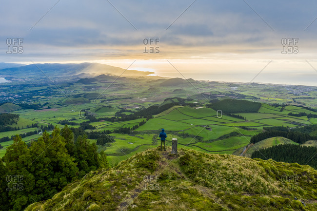 Aerial view of a hiker looking over Sao Miguel island landscape at sunset on Azores archipelagos, Portugal