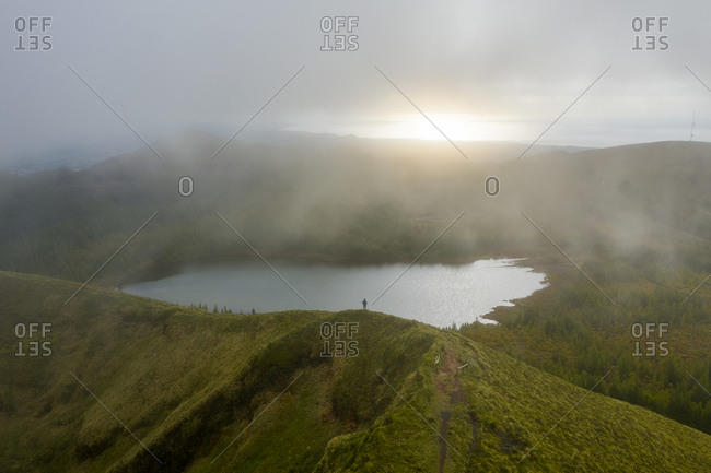 Aerial view of a man standing on the top of the hill looking at Lagoa Rasa lake on Azores archipelagos on Sao Miguel island, Portugal.