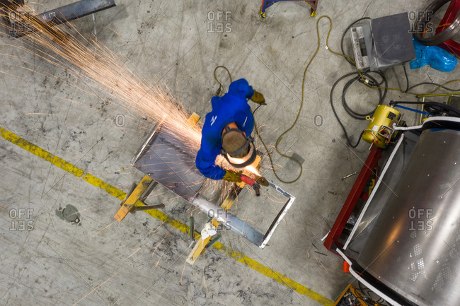June 26, 2019: Chicago, Illinois17 April 2019: Aerial view of a man working alone in a warehouse sawing metal with a grinder