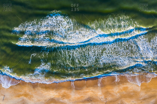 Aerial view of crispy waves of North Atlantic Ocean breaking on the sandy beach of Anastasia Island in Florida, United States of America