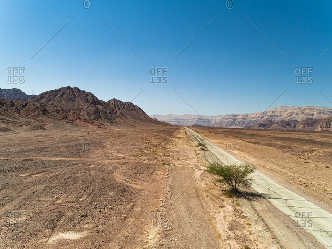 Aerial view of old road in a desert landscape with a tree. Timna park, Negev, Israel.