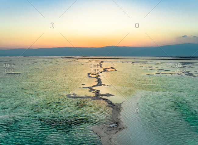 aerial view of sunrise over colorful salt veins in the Dead Sea and mountains on the horizon. Dead Sea, Negev, Israel.