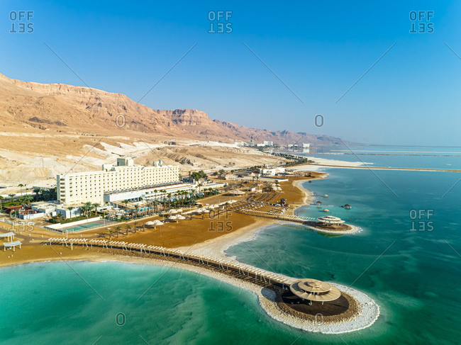 Aerial view of beach and hotels with in-sea gazibo and the Judaean Mountains in the background. The Dead sea, Negev, Israel.