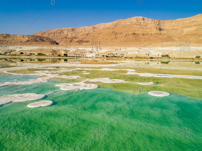 Aerial view of circle salt formation in the colorful water of Dead sea and mountains in the horizon. Dead sea, Negev, Israel.
