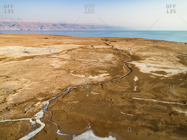 Aerial view of a long and dry salt river stream in the northern part of the dead sea, Jordan Rift Valley, Israel.