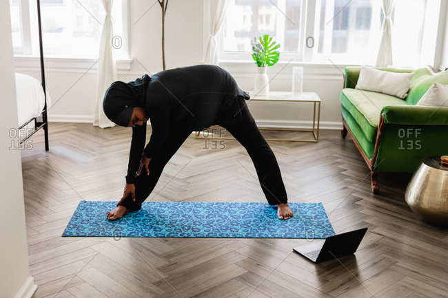 Black Muslim Woman Does Yoga at home, wearing a Sport Hijab