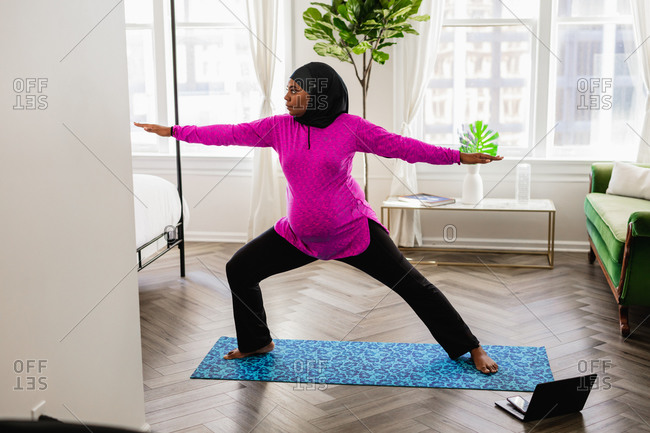 Black Muslim Woman Does Yoga at home, wearing a Sport Hijab, watching online tutorial instructional video