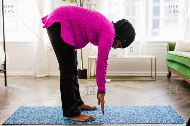 African American Muslim Woman stretches at home
