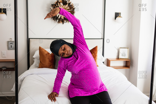 Pregnant Muslim Woman does bedside maternity yoga and stretches at home