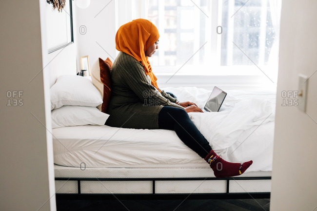 Black woman works from home on laptop in bed, wearing hijab, video conference call