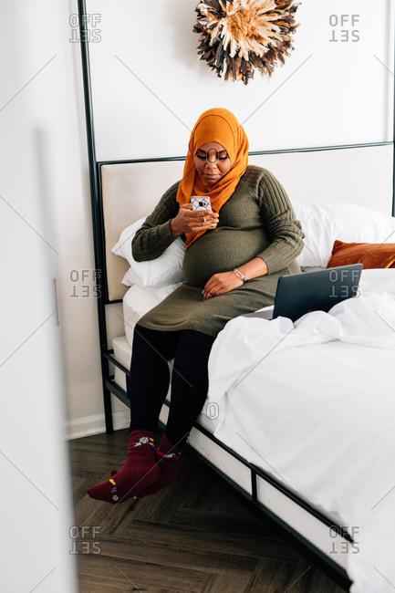 Black pregnant women sitting on bed at home