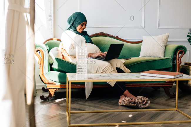 Professional Black woman working from home laptop, wearing a Hijab on video conference chat