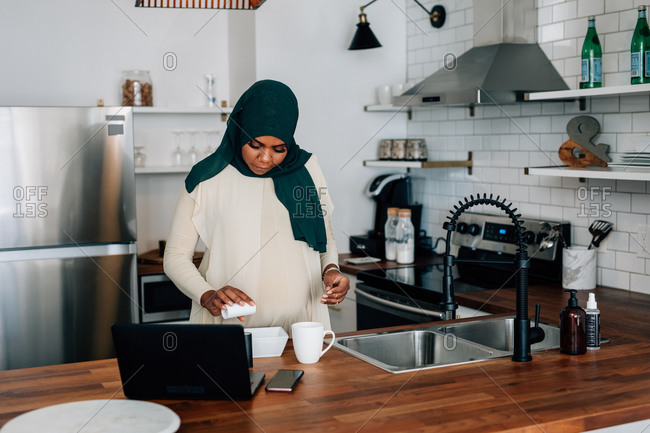 Black Pregnant woman prepares snack in kitchen at home, wearing a Hijab