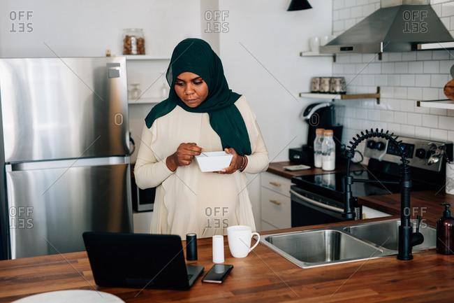 Black woman working from home at kitchen counter, Muslim