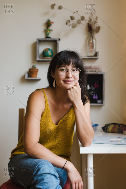 Confident young mixed race jewelry designer sitting by her desk at home and posing