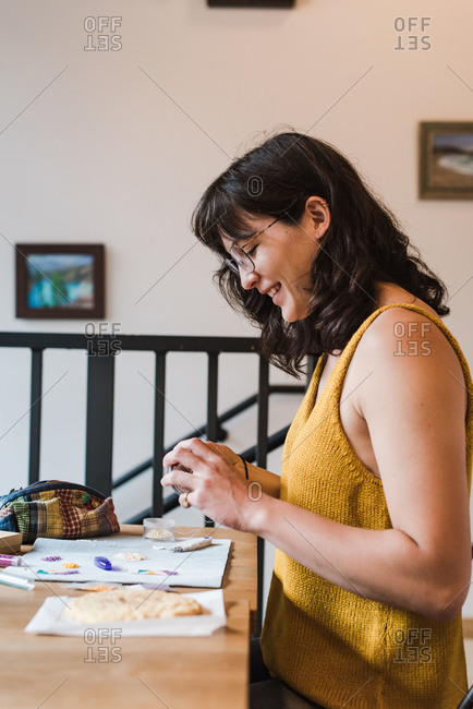 Side view of a small business owner making jewelry at a table in her home