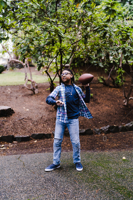 Bespectacled young boy in a checkered shirt throwing a football with his left hand