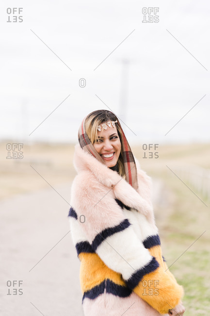 Beautiful Muslim woman laughing heartily wearing a fur coat