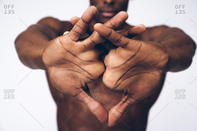 Muscular black man stretching his muscles with his arms outstretched in front of him