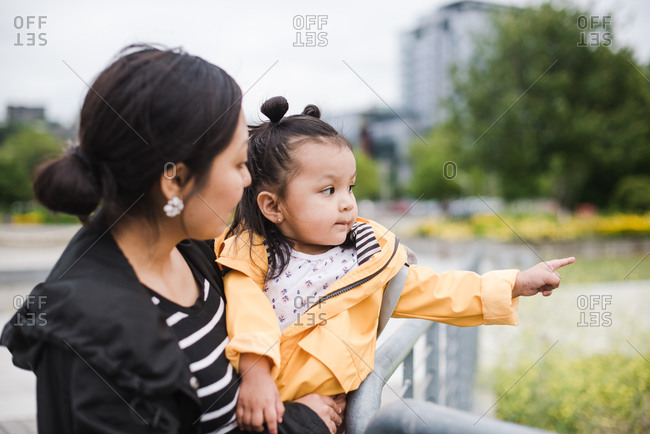 Wide shot of a little girl pointing at something to show her mother