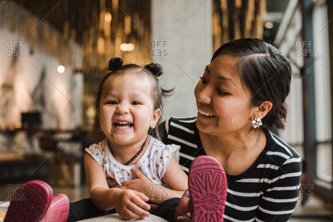 Wide close up shot of a mother and daughter laughing in a lounge
