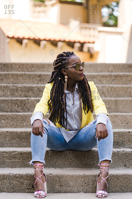 Stylish young girl with dreadlocks sitting on stairs and posing confidently