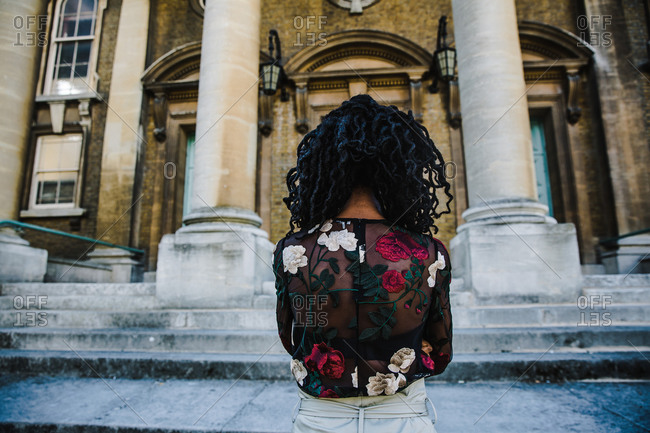 A back shot of a black woman with braided hair style wearing a floral dress