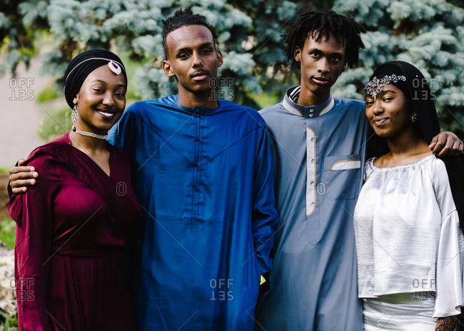 Two young black Muslim men standing with two black Muslim women in Islamic clothing