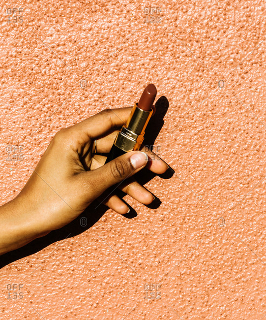 Vertical shot of a woman's hand holding a lipstick against an orange wall