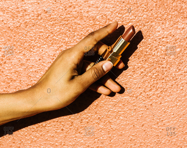 Close up of a woman's hand holding a lipstick against an orange wall