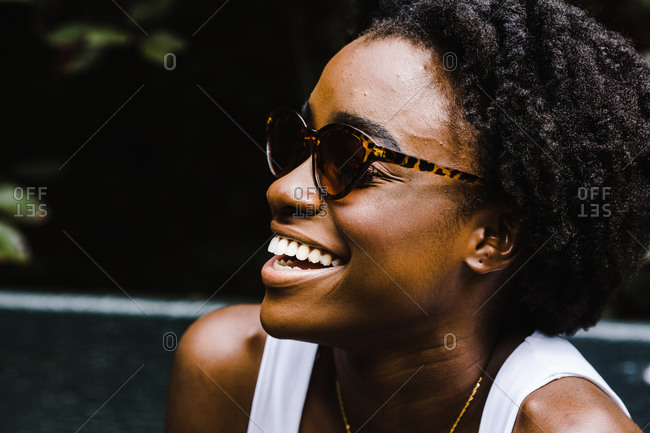 Close up portrait of a black woman smiling with her sunglasses on