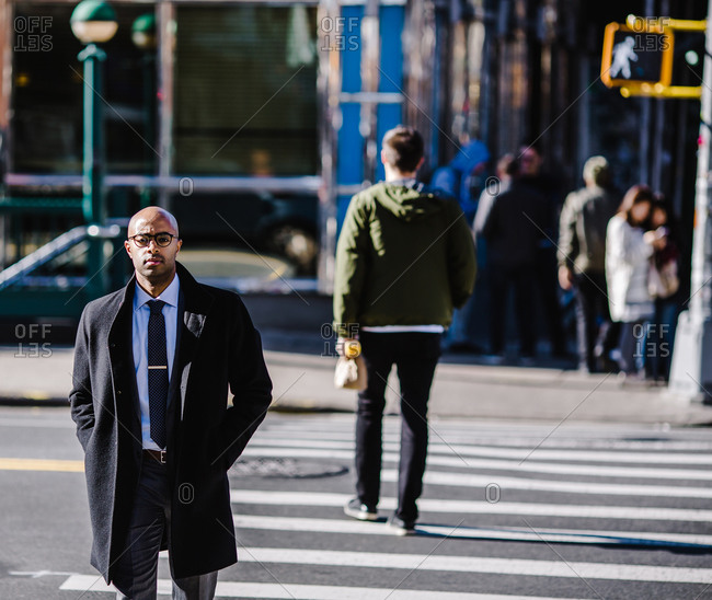 Medium shot of a bald black man in a heavy coat walking across a pedestrian crossing outside his office building