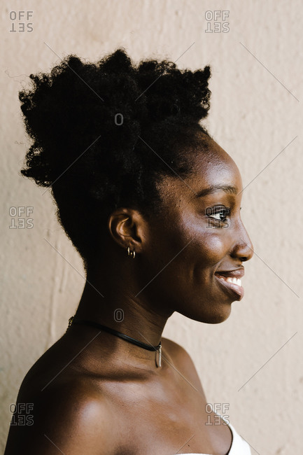 Vertical shot of a black woman with two afro puffs smiling and standing in front of a wall