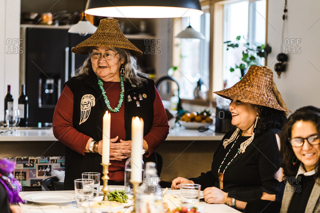 Horizontal shot of an elderly head woman addressing her fellow native american women gathered around the dinner table