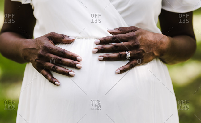 Close up shot of a woman in a white dress holding her pregnant belly