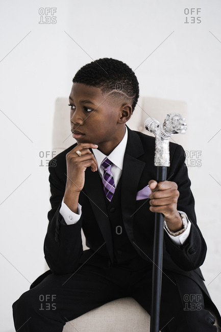 Vertical three quarter length portrait of a boy in chair holding a fancy cane in a black suit looking sideways