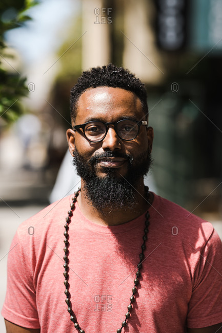 A black man with facial hair wearing glasses, red t-shirt, and necklace