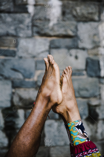 Vertical shot of the feet a black man and woman touching during a yoga stretch