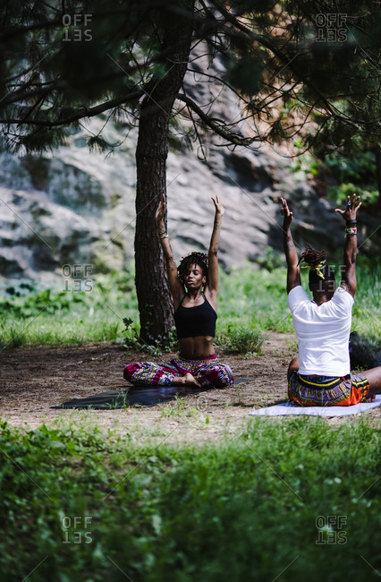 Vertical wide shot of a black man and woman doing yoga outside