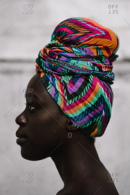 A side profile vertical close up shot of an African woman wearing a multicolored headwrap