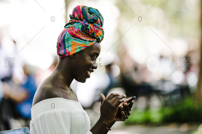 A side profile shot of a happy african woman in a colorful headscarf using a smartphone