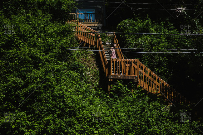 Wide shot of an Iranian man standing on a staircase surrounded by trees