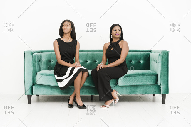 Horizontal shot of mother and daughter sitting on a green couch look sideways