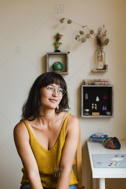 Young, confident mixed race jewelry designer sitting on her chair next to the desk and wishfully looking into the distance