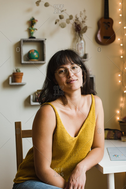 Vertical shot of a young mixed race jewelry designer leaning on her desk and looking at the camera