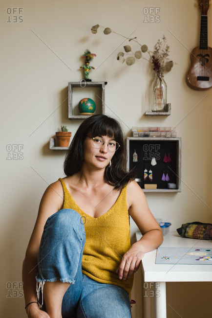 Vertical shot of a young mixed race businesswoman sitting by her desk while making her own jewelry at home