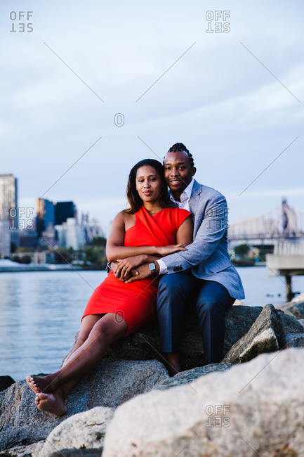 Vertical portrait of a seated young couple with the man embracing his partner over the boulders by waterfront look at the camera