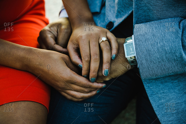 Close up shot of an engaged couple holding hands dressed in smart casuals