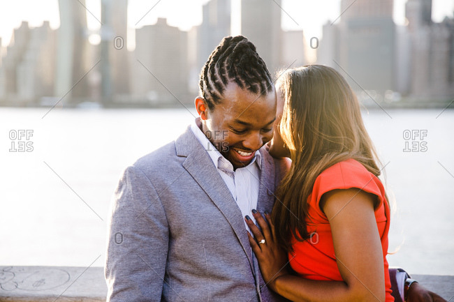 Couple shares a light moment near a waterfront