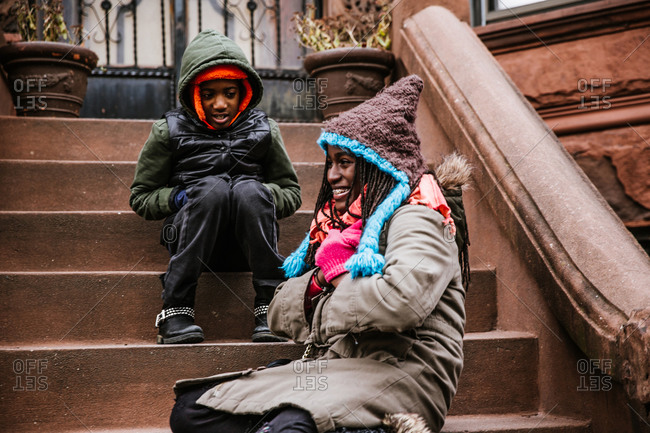 Black brother and sister sitting on apartment steps